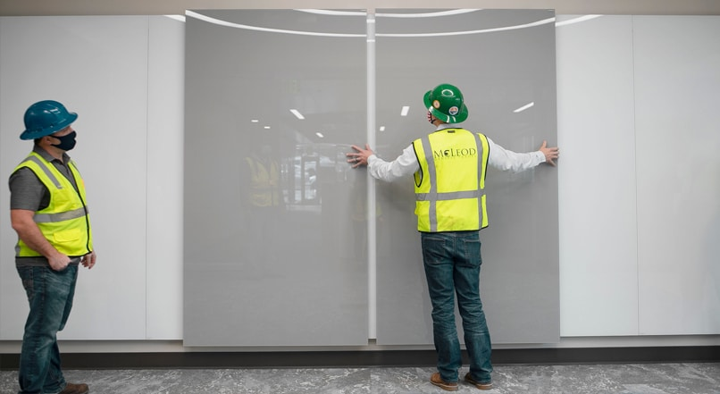 Man in hard hat and reflective vest with his arms spread on a wall as another man looks on