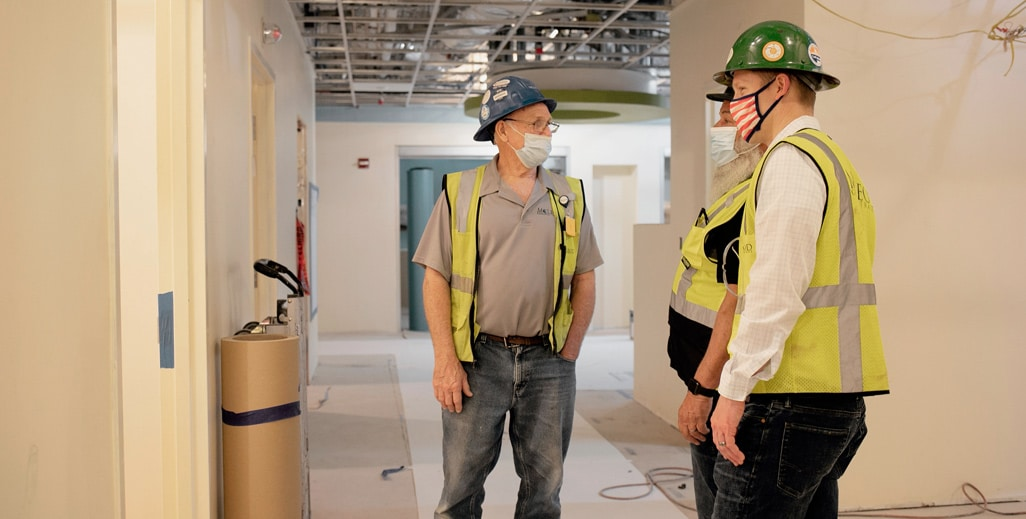 Three men in reflective vests and hard hats talking inside a building
