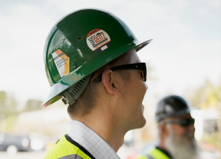 Closeup of a man's hard hat and sunglasses