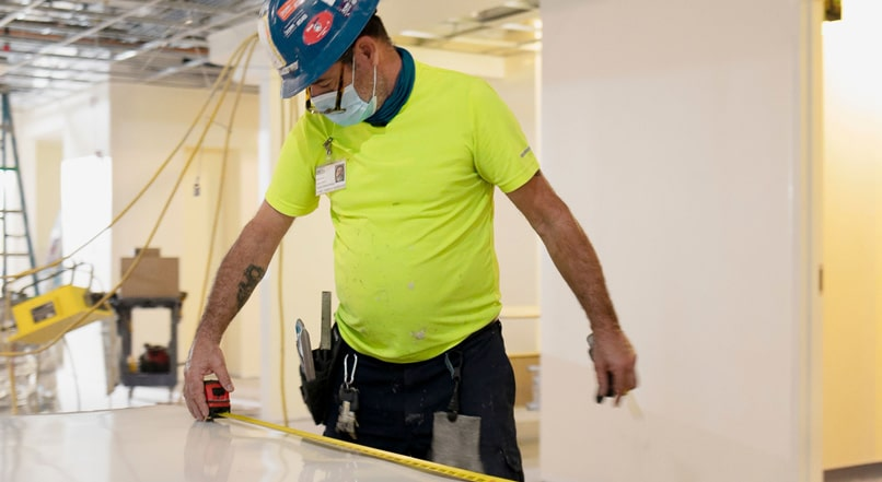Man in hard hat and lime green shirt measuring a surface