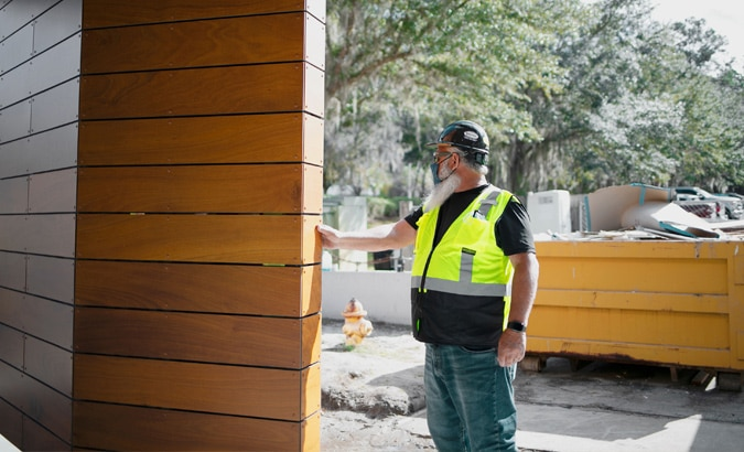 Exterior view of man in hard hat and reflective vest touching exterior wooden wall